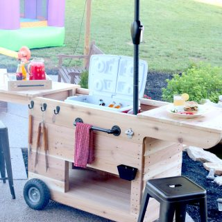 Outdoor party station mobile cart featuring storage for a large cooler, drawer that pulls out and doubles as a serving tray, pipe towel bar, and kiddie table! So COOL!