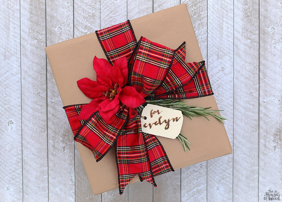 Dressing up kraft paper is easy with some pretty ribbon, sprigs of rosemary, and a wood-burned gift tag