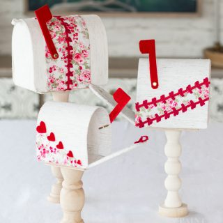Easy DIY Valentines Mailboxes made from fabric, cardboard, and wooden candle sticks.