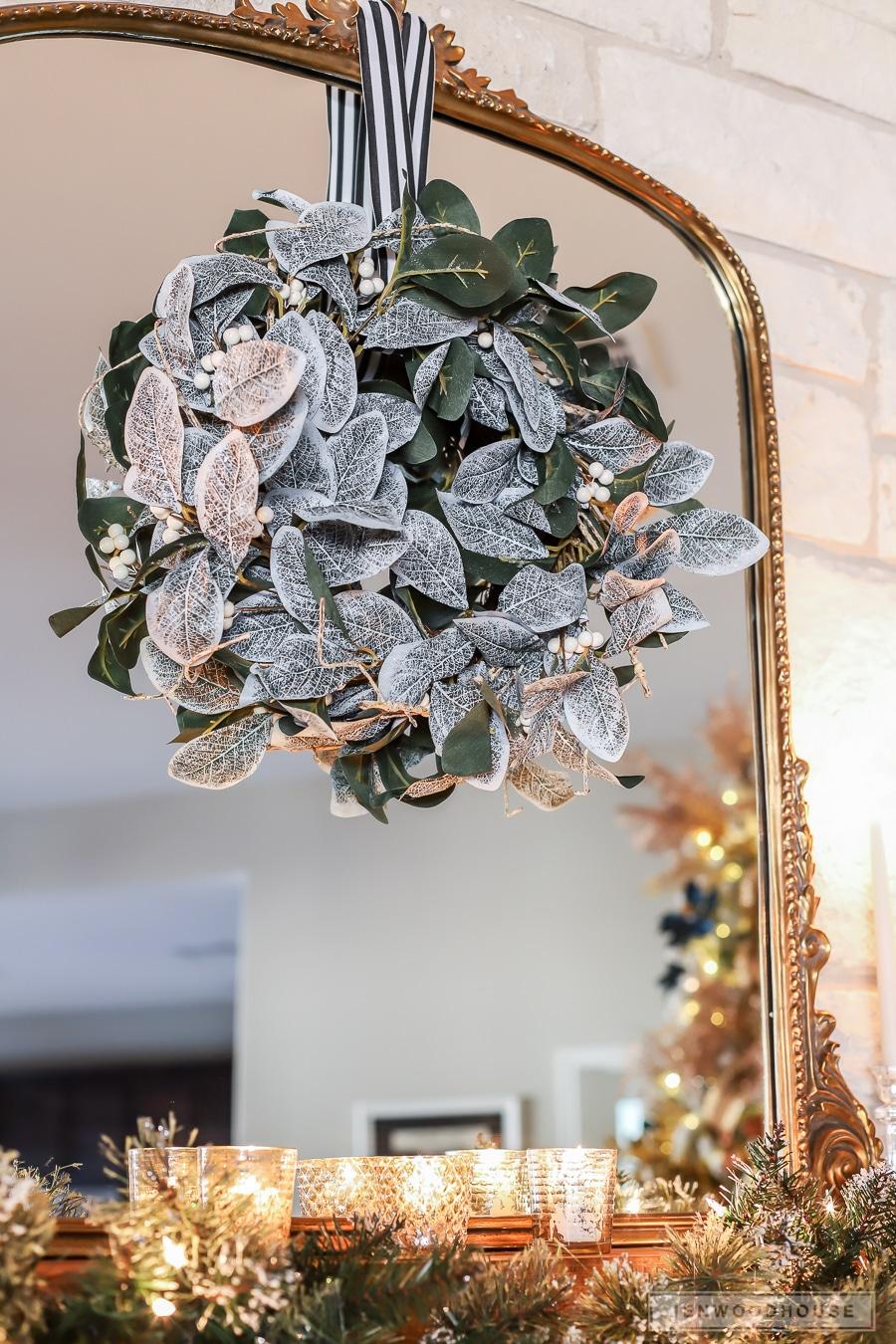 Magnolia wreath and antique mirror over mantel