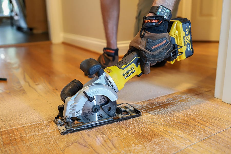 Dewalt mini circular saw cutting hardwood flooring