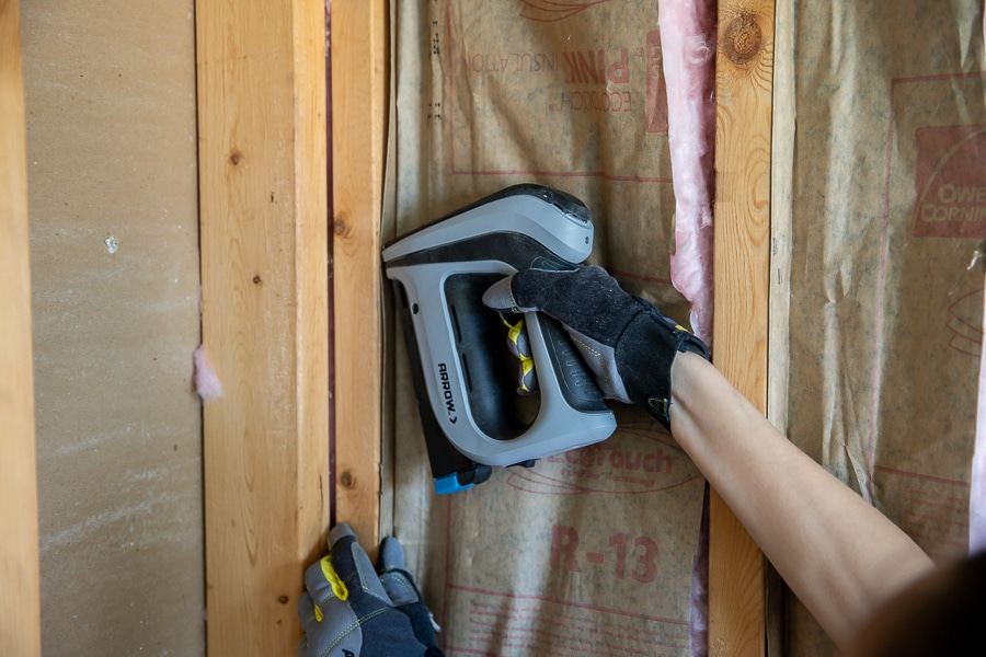 Use a staple gun to attach insulation to the studs