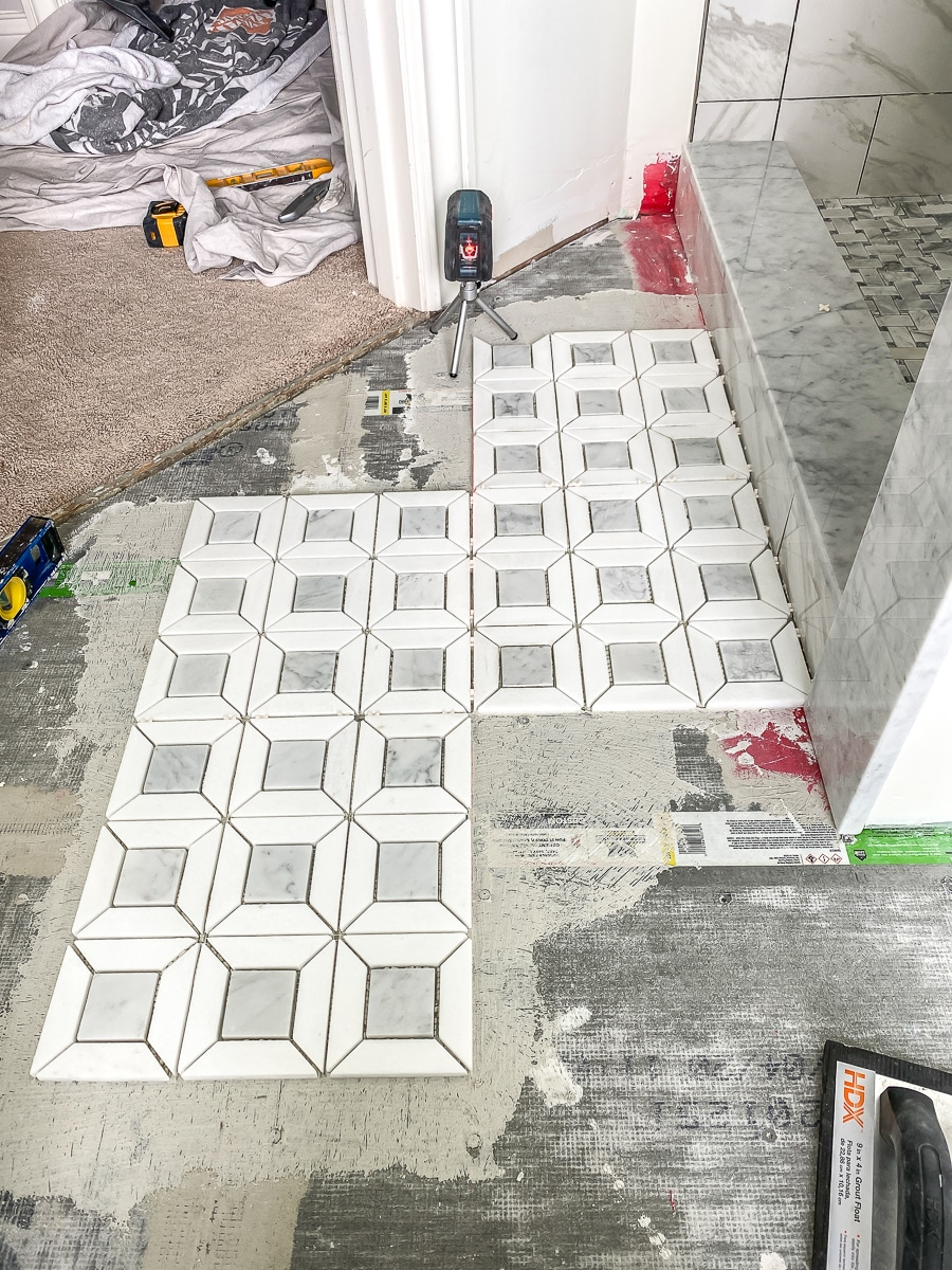 Tiling the bathroom floor with marble mosaic tiles