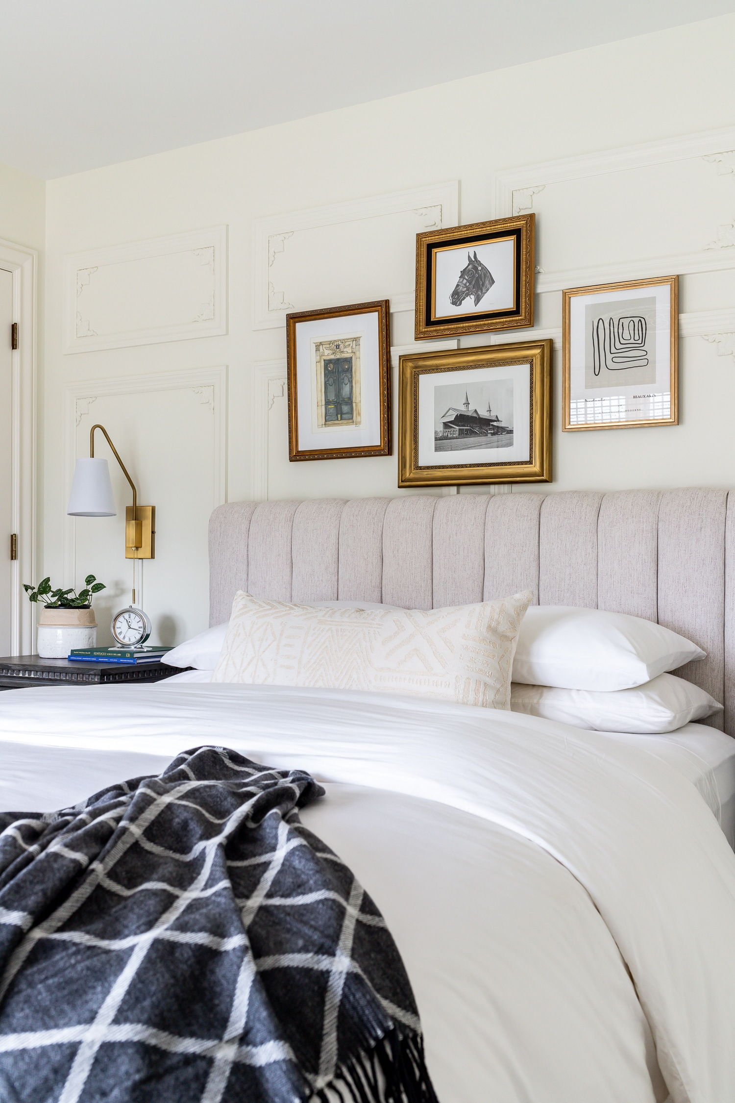 Art gallery with vintage frames above bed