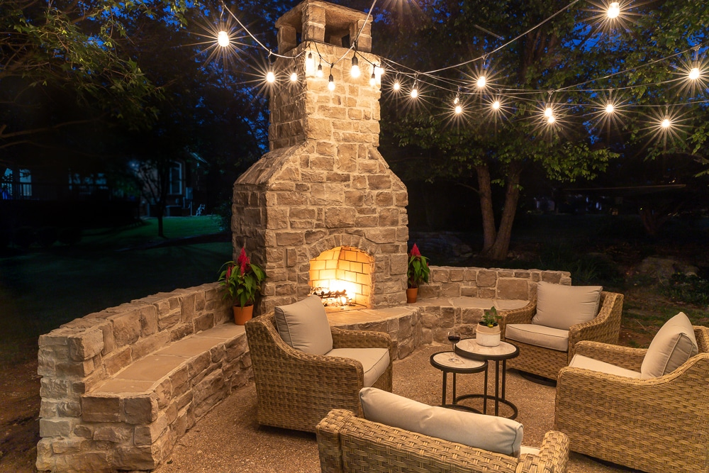 Beautiful patio space featuring an outdoor fireplace with bench seating
