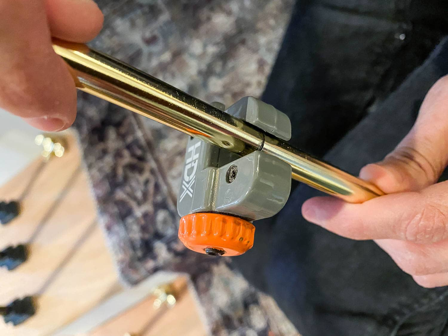 Cutting brass stair rods to length with a pipe cutter
