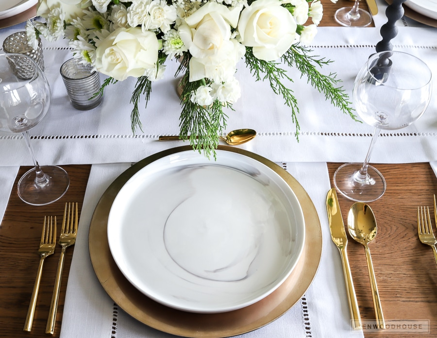 Winter White Christmas table setting with marble plates and gold flatware